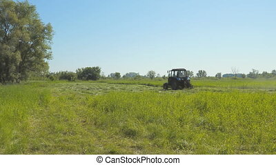Tractor mowing grass in meadow - Tractor mowing grass in the...