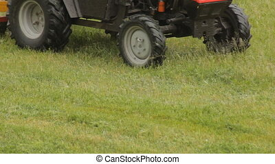 Tractor mows the grass in the rain, close-up, lawn mower