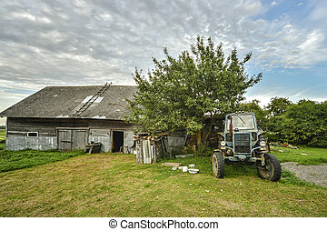 Tractor near the village house. Rural landscape in summer.