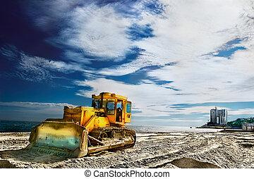 Tractor on a sandy beach near the sea