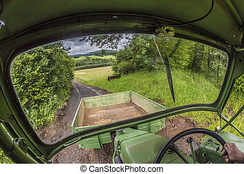 tractor on a small road between fields - tractor on a small...
