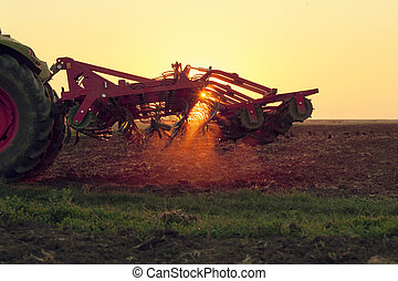 Tractor on sunset doing agriculture