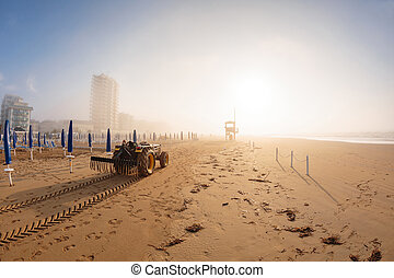 tractor on the sandy beach cleaning, after winter, preparation for the holiday season in Italy. Wooden trunks in on the seashore after a sea storm. dense sea breeze at dawn