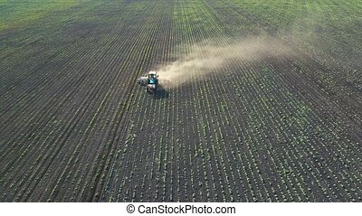 Tractor performs seeding on the field (top view from height)