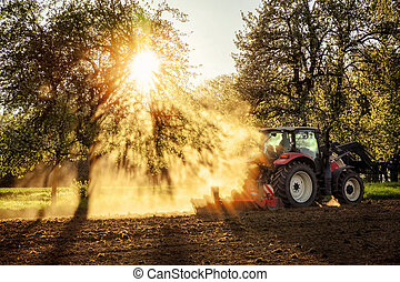 Tractor ploughing a field at sunset - Tractor plowing a...