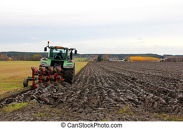 Tractor Ploughing a Field in Autumn - Tractor ploughing a...