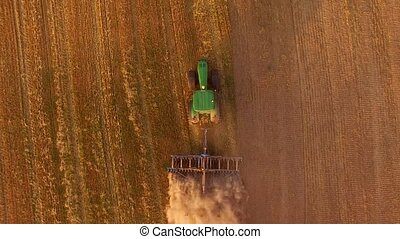 Tractor ploughing field, top view. Green tractor pulling...