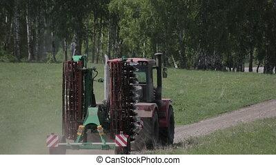 Tractor plow field near forest in summer.