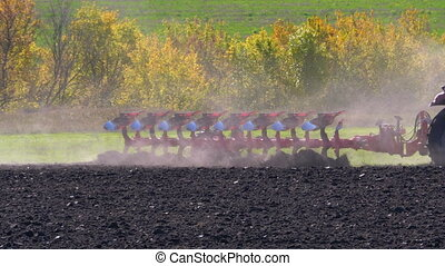 Tractor Plow Plowing Field. Farmer sowing and cultivating...