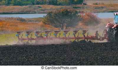 Tractor Plow Plowing Field. Slow Motion in 4K. Farmer sowing...