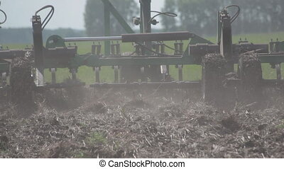 Tractor Plowing a field Plow closeup. soil, grass, spring sowing