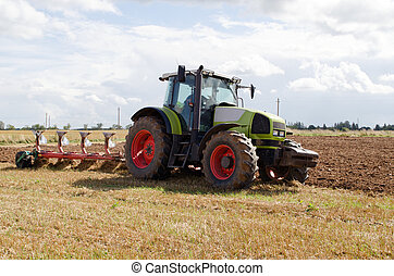 tractor plowing agricultural field autumn