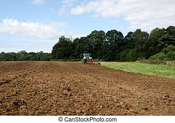 tractor plowing agricultural field summer