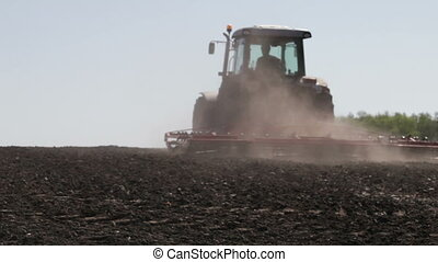 SMELA, CHERKASSKAYA/UKRAINE - APRIL 10 2013: Tractor plowing as much dust and leaves worth on April 10 in Smela