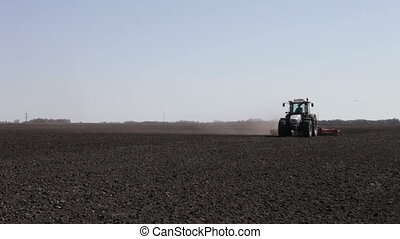 tractor plowing black field boundless with dust