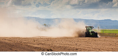 Tractor plowing dry farm land - Panorama of a tractor...