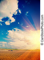 Tractor plowing field in spring on sunrise instagram stile