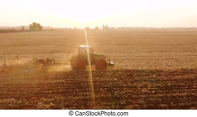 Tractor plowing field in sunlit. Farm tractor cultivating field after harvesting. Preparing land for sowing.
