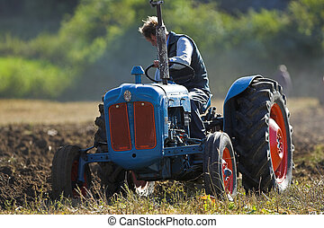 Tractor plowing field - Agricultural Tractor ploughing a...