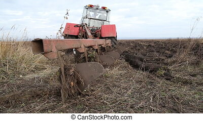 Tractor plowing land - Old tractor with a large plow plowed...