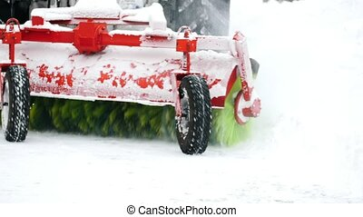 Tractor plowing snow on street, close up