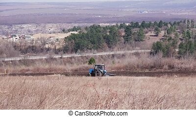 Tractor plows a field in spring