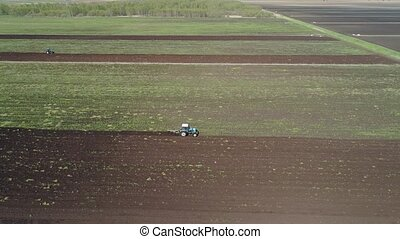 Tractor plows farm land. - Aerial view of tractor plows the...