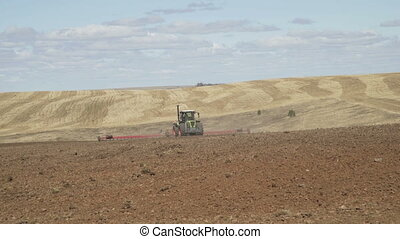 Tractor plows field with plows before sowing. Agricultural...