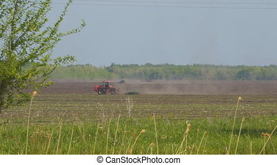 Tractor plows or harrows the ground on the field....