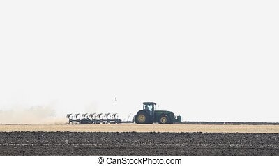 Tractor plows the land in the field