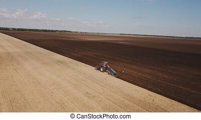 tractor plows the land with a plow a bird's-eye view