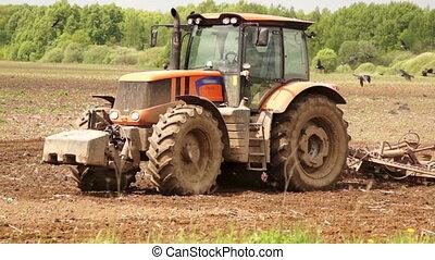 Tractor preparing land for sowing cereal crop, rural scene