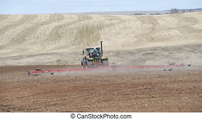 Tractor preparing land with seedbed cultivator in farmlands....