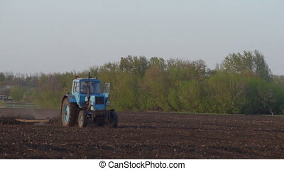 Tractor Processing Field - Farmer sowing a plowed field with...