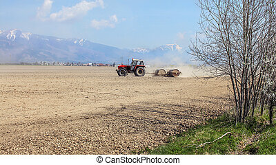 Tractor pulling heavy metal roller over dry field, with mountains, little bit snow on top, in background. Spring field preparation.