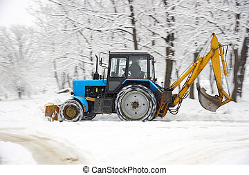 Tractor removes snow in a park