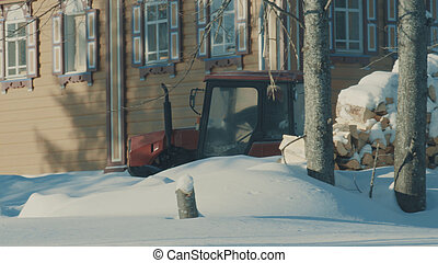 Tractor removing snow from the winter road in the forest