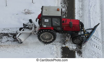 Tractor removing snow from walkways. Slow motion