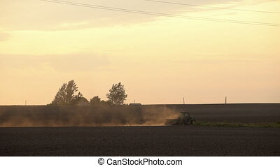 Tractor seeding field near country houses. Sunset sky....