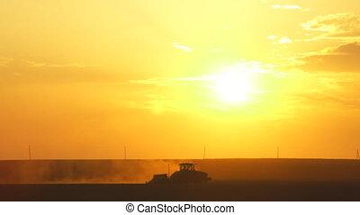 Tractor seeding plantation. Sunset sky on background. Static...