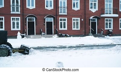 Tractor shoveling away snow in residential area