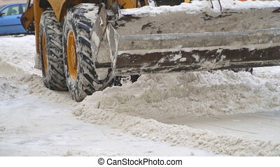 Tractor shoveling snow on the street. Slow-motion.