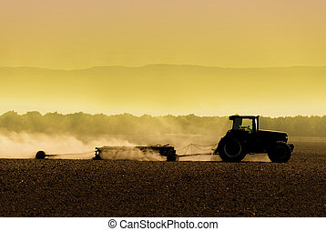 Tractor Silhouette - Muted, yellow, backlit silhouette of...
