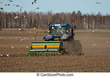 Tractor sowing seed - tractor at work on a field and wild...