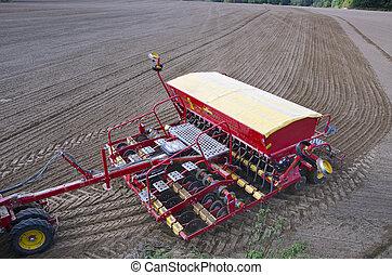 Tractor sowing seeds in freshly plowed field