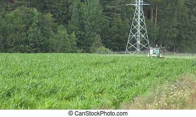 Tractor spray fertilize maize field with chemical near road....