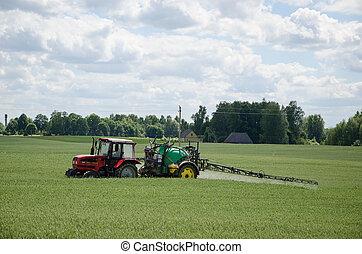 tractor spray green crop field in summer