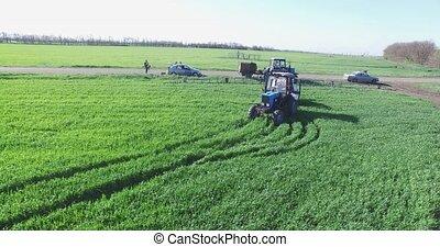 Tractor sprayer spraying wheat in spring. - Tractor spraying...