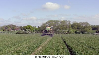 Tractor Spraying a Controversial Glyphosate Herbicide on Agricultural Land