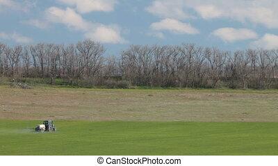 Tractor spraying field in spring